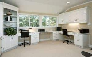 large home office area, three work areas with cabinets and book shelves, two large windows
